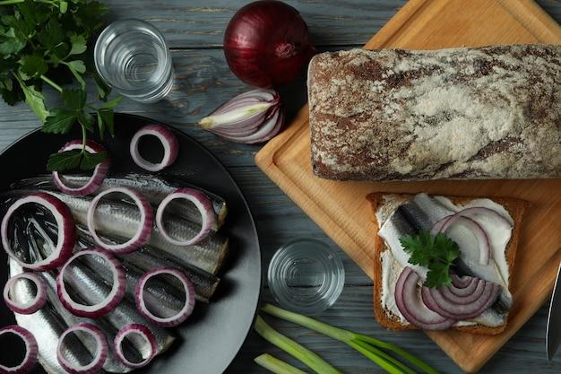 Рюмки водки и вкусные закуски на деревянном столе, вид сверху