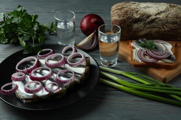 Рюмки водки и вкусные закуски на деревянном столе