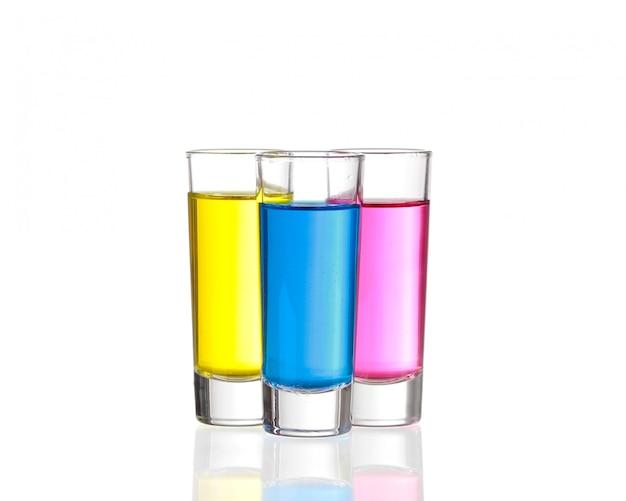 Shots - три красочных напитка на белом фоне с отражениями