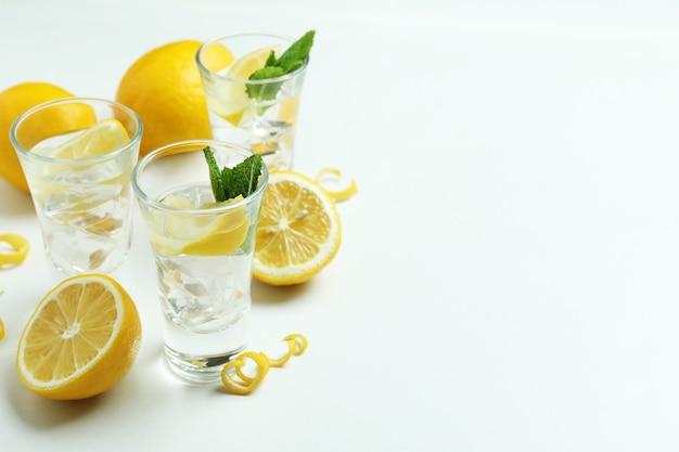 Shots of vodka and lemons on white