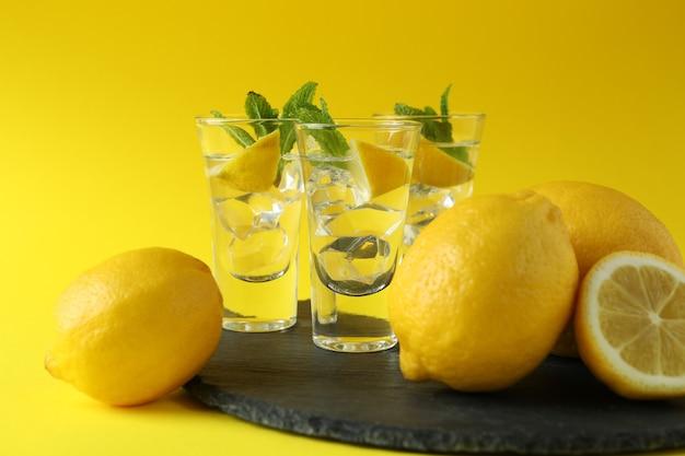 黄色い表面のトレイにレモンスライスとミントを使ったショット