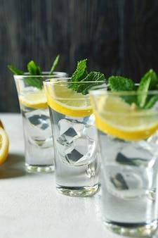 白い織り目加工のテーブルにレモンスライスとミントのショット