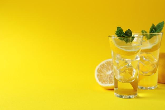 黄色い表面にレモンスライスとミントを使ったショット