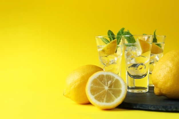 Shots with lemon slice and mint on tray on yellow surface