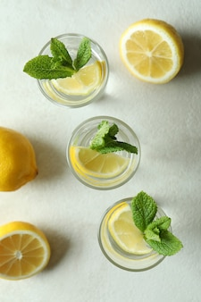 Shots with lemon slice and mint on white textured table