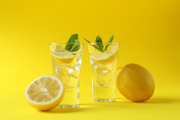 Shots with lemon slice and mint on yellow surface