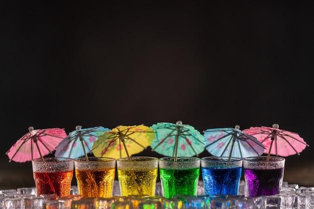 Столы с разноцветным спиртом, стоящие в ряд и украшенные коктейльными зонтиками