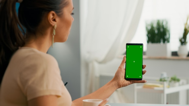 Over shoulder of business woman using isolated smartphone with mock up green screen chroma key sitting on table desk, while talking with her friends during online videocall sitting on office desk