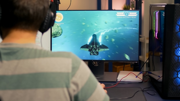 Over shoulder footage of professional streamer playing digital space shooter video games on computer using headphones, microphone and mouse