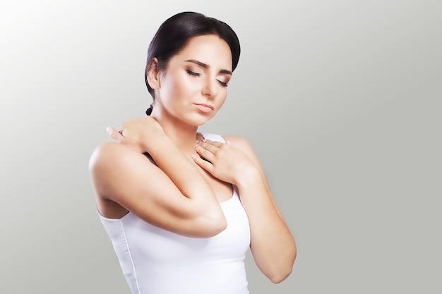 Боль в плече. женщина держит две руки за шею и плечи. вывих. холодно. мышечное напряжение концепция здоровья.