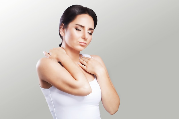 Shoulder pain. the woman holds two hands over the neck and shoulders. dislocation. cold. muscle tension the concept of health.