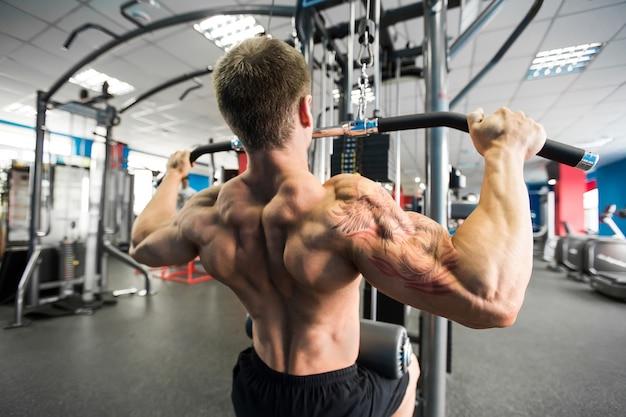 ショルダープルダウンマシン。ジムでラットプルダウントレーニングをしているフィットネスマン。背中上部の体力トレーニング。