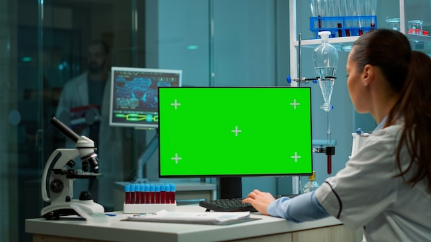 Over the shoulder shot of chemist working with green screen mock-up template on desktop computer, isolated display, chroma key. in background scietist doctor enter in medical lab with blood sample.