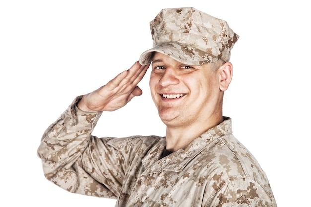 白い背景に分離された、カモフラージュ戦闘服とパトロールキャップで笑顔のアメリカ陸軍兵士、海兵隊の歩兵または軍の請負業者の肩のスタジオの肖像画は、手の敬礼を示しています