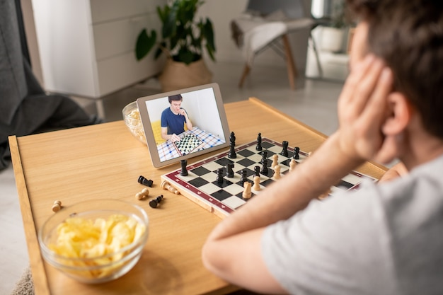 Over shoulder view of man sitting at coffee table and deciding about chess move while playing with friend via video chat
