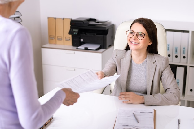 Over shoulder view of senior lady giving filled form to smiling friendly social worker in office