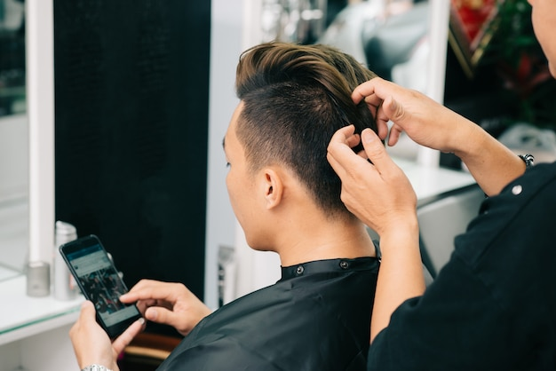 Over the shoulder view of unrecognizable cropped hairdresser applying wax on hair of client