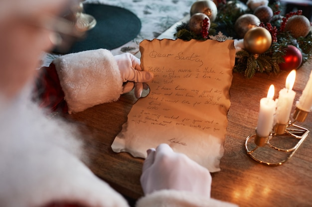 Over shoulder view of unrecognizable santa claus in white gloves sitting at table with burning candl...