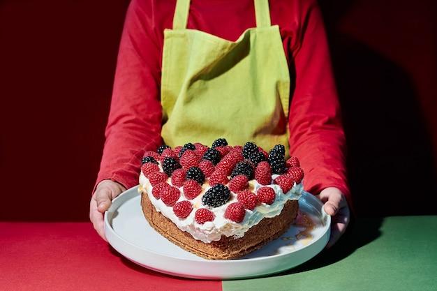 Плечи и руки ребенка в зеленом фартуке показывают торт в форме сердца из ягод, ежевики и малины.