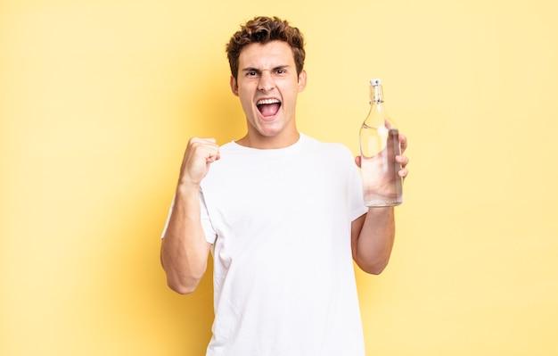 Агрессивный крик с гневным выражением лица или со сжатыми кулаками, празднуя успех. концепция бутылки с водой