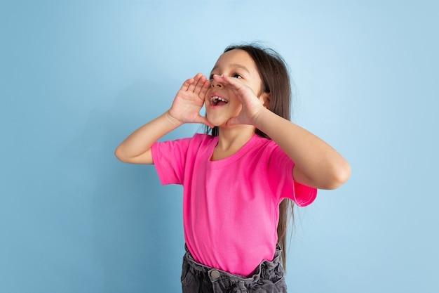 叫び、呼びかけ。青い壁に白人の少女の肖像画。ピンクのシャツの美しい女性モデル。人間の感情、顔の表情、若者、子供時代の概念。