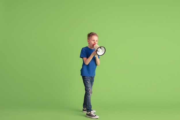 叫び、呼びかけ。緑の壁で遊んで楽しんでいる幸せな少年。明るい布の白人の子供は、遊び心のある、笑顔に見えます。教育、子供時代、感情、表情の概念。