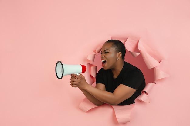 叫ぶ。陽気なアフリカ系アメリカ人の若い女性は、感情的で表現力豊かな、引き裂かれた珊瑚紙でポーズをとります。