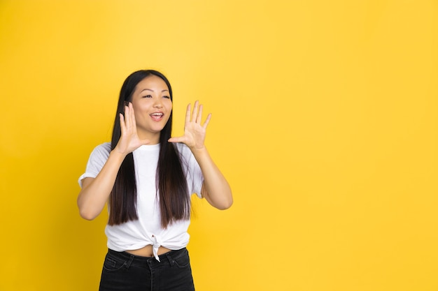 Shouting. portrait of young asian woman isolated ce.