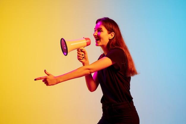 グラデーション青黄色スタジオで若い白人女性を指すメガホンで叫ぶ