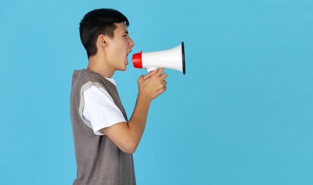 Кричать в мегафон. портрет молодого кавказского человека на красной предпосылке студии с copyspace. красивая мужская модель. понятие человеческих эмоций, выражения лица, продаж, рекламы, молодежи. листовка