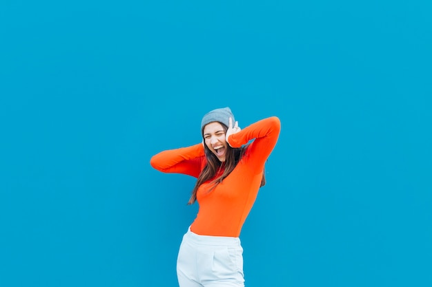 Shouting woman with her hands on ear wearing knit hat over blue background