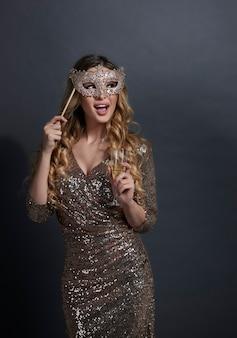 Donna gridante con la maschera che beve champagne