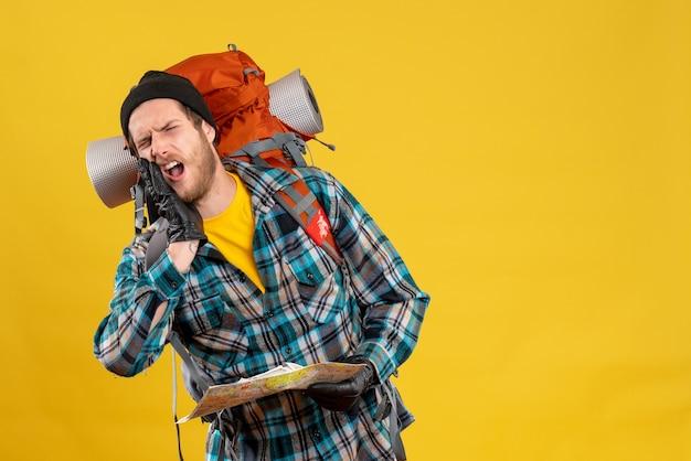 Gridando giovane zaino in spalla con cappello nero che tiene mappa