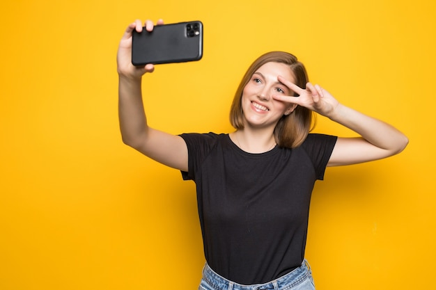 Shouting young woman taking a selfie photo on yellow wall.