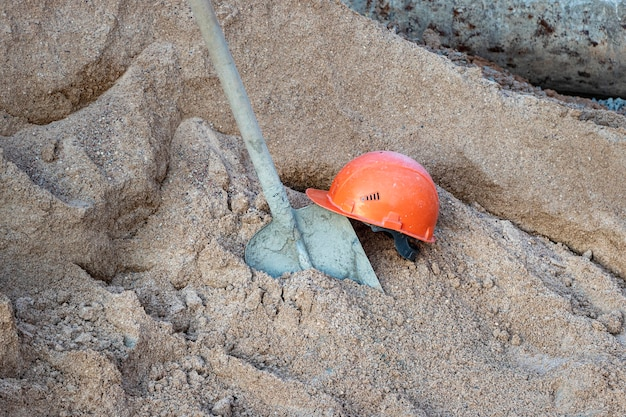 A shovel covered in concrete in a pile of sand to prepare concrete and an orange construction worker's helmet.