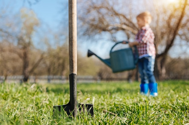 A shovel digging soil with a little boy on the background watering a vernal lawn with a green pouring pot