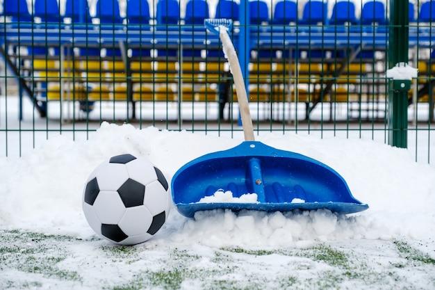 シャベル、雪に覆われたサッカー場、クラシックなサッカーボール