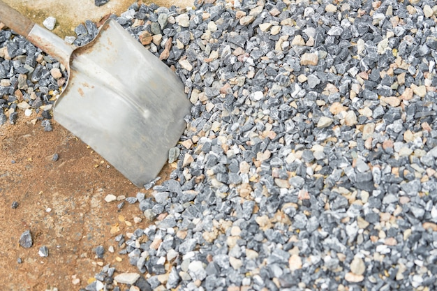 Shovel on stone for construction material in house building concept