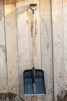 Лопата весит на стене деревянного сарая