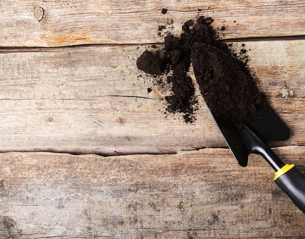 Shovel with dirt on wooden table