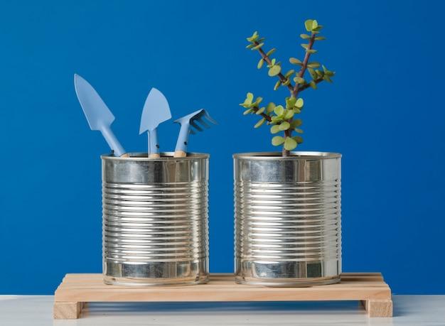 木の板の青い背景にリサイクル缶の土と植物のシャベル