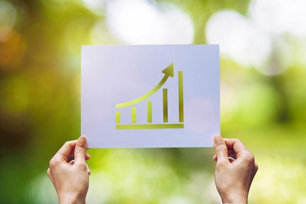 ビジネスペーパーのグラフ統計を表示し、自然の背景に手元のグラフを示す矢印