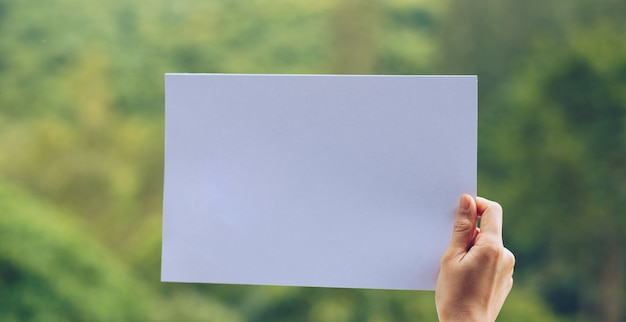 Show business paper in hand on nature background