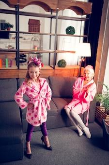 おばあちゃんのために表示します。かかとの高い靴を試して、おばあちゃんのためのファッションショーを作るヘアローラーの面白い女の子