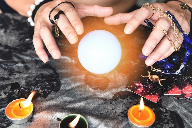 Покажите гадалок с руками, держащими карты таро и гадалку со свечой и волшебным хрустальным шаром, выполнение чтений, магические представления, вещи, мистические астрологи, прогнозирующая концепция