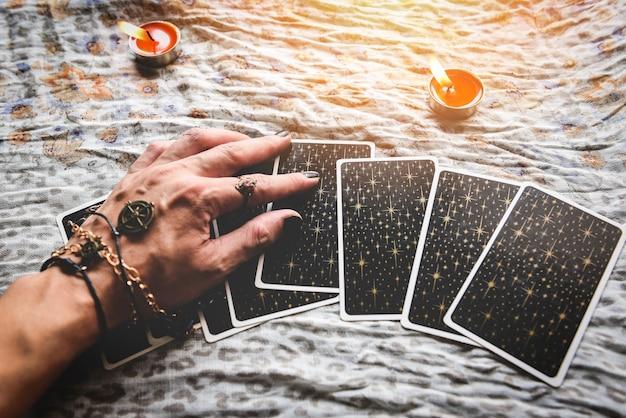 타로 카드를 들고 있는 점쟁이와 테이블에 촛불을 든 타로 판독기, 마법 같은 공연 읽기, 신비로운 점성술 예측 개념
