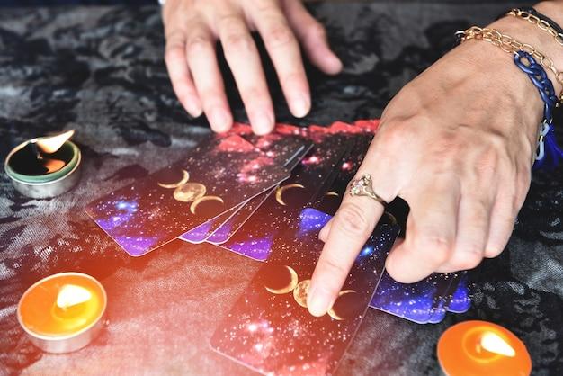 Покажите гадалок с руками, держащими карты таро, и гадалку со свечой на столе, выполнение чтений, магические представления, вещи, мистические астрологи, предсказывающие концепцию