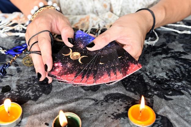 Покажите гадалок с руками, держащими карты таро, и гадалку со свечой на столе, выполнение чтений, магические представления, вещи, мистические астрологи, прогнозирующие концепцию