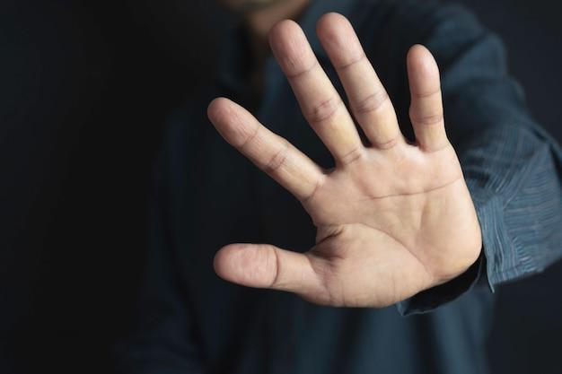 黒の背景に停止ジェスチャーで手を見せる