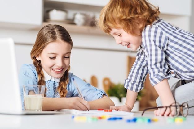 메모를 보여주세요. 그의 형제 옆에 바로 테이블에 앉아 집에서 그녀와 함께 주말을 보내는 동안 그녀를 재미있게 만드는 재미 있고 매력적인 빨간 머리 소년